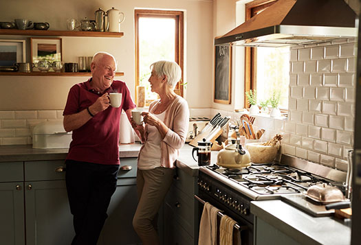 Retired couple smiling in the kitchen, retirement savings