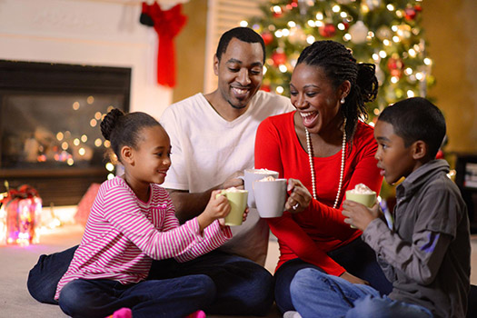 Family drinking hot chocolate by the Christmas tree during the holiday season