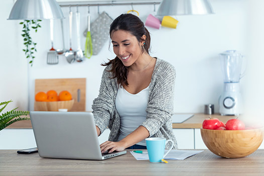 A young woman on her computer working on her side hustle at home